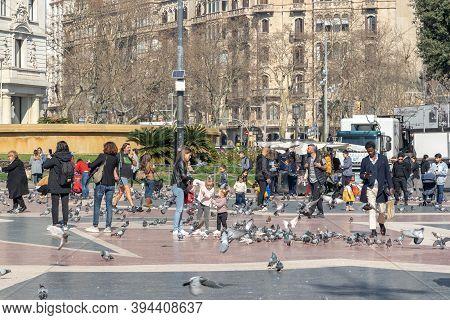 Barcelona, Spain - Feb 24, 2020: Pedestrians Feed Pigeons On Plaza De Catalunya On Sunny Afternoon