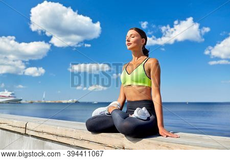fitness, sport and yoga concept - young woman meditating in lotus pose at seaside