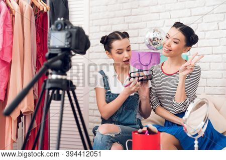 Two Fashion Blogger Girls Hold Up Eye Shadows And Brushes To Camera.