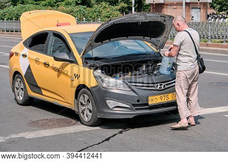 Moscow \ Russia 06 10 2019: Driver Yandex Taxi Saves The Car From Overheating On A Hot Day. Taxi Dri