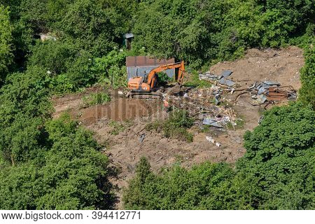 Excavator Demolishes Illegal Buildings In The Forest. Destroy Of An Illegally Built Old Building In