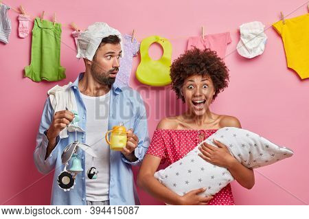 Child Birth, Parenting, Fatherhood And Motherhood Concept. Young Busy Parents With Infant, Busy Mult