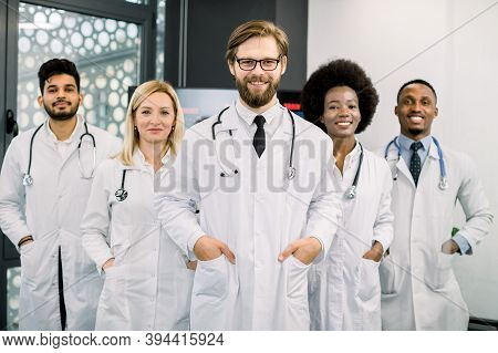 Successful Team Of Multiracial Male And Female Medical Doctors In White Coats, Looking At Camera And
