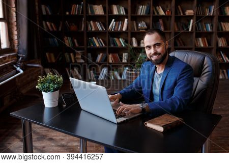 A Young Businessman Works On A Laptop In A Luxurious Office In The Library. A Bearded Cheerful Man I