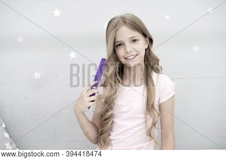 Enjoying Her Beauty. Child Curly Hairstyle Hold Hairbrush Or Comb. Comb Hair Before Go To Sleep. Hai