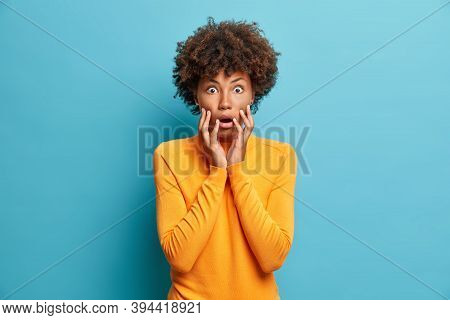 Scared Dark Skinned Young Woman Stares Bugged Eyes And Holds Face Keeps Mouth Opened Wears Casual Ju