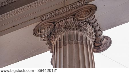 Decorative detail of an ancient Greek column. Architecture detail close up of column top. Classic pillar of ionic order. Old marble capital