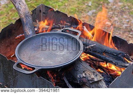 Firing A Cast Iron Skillet Over An Open Fire. Cast Iron Skillet Over An Red Fire Heats Up For Furthe
