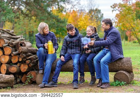 family relaxing outdoor in autumn city park, happy people together, parents and children, they drink tea and eat sandwiches, talking and smiling, beautiful nature