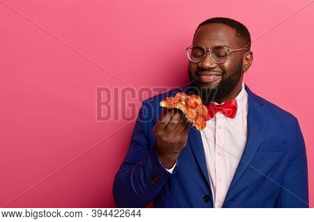 Appetizing Of Junk Food. Pleased Dark Skinned Afro American Man Smells Delicious Pizza, Being Hungry