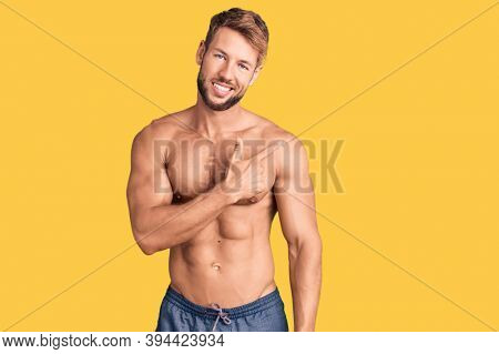Young caucasian man standing shirtless cheerful with a smile of face pointing with hand and finger up to the side with happy and natural expression on face