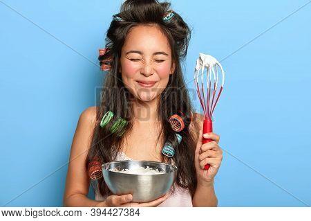 Photo Of Joyful Brunette Woman Keeps Eyes Shut, Enjoys Cooking Process, Holds Whisk With White Cream