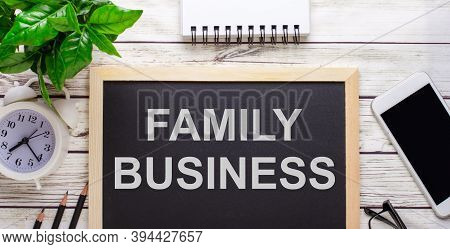 Family Business Written On A Black Background Near Pencils, A Smartphone, A White Notepad And A Gree