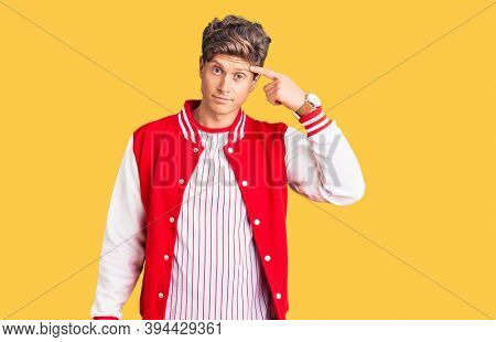 Young handsome man wearing baseball uniform pointing unhappy to pimple on forehead, ugly infection of blackhead. acne and skin problem