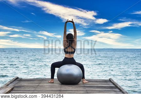 Young Healthy Woman Practicing Yoga Ball On The Bridge In The Nature. Healthy Concept.