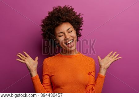 Emotional Dark Skinned Woman Gestures Actively, Raises Palms, Laughs Positively, Has Upbeat Mood, We