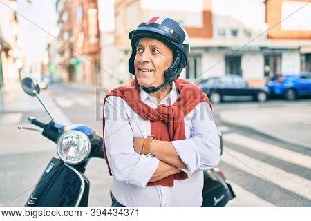 Senior motorcyclist man smiling happy wearing moto helmet at the city.