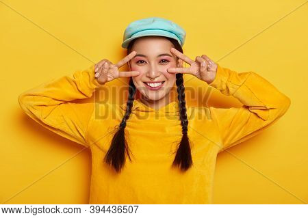 Horizontal Shot Of Carefree Smiling Asian Lady Makes Victory Peace Gesture Near Eyes, Has Happy Mood