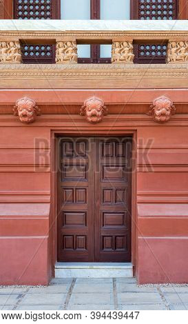 Recessed Engraved Closed Wooden Door Installed In Ornamental Stone Wall Outside Of Old Building With