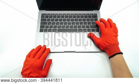 Hands In Red Protective Gloves Lie Next To The Laptop, Close Up View. Concept Of Network Communicati