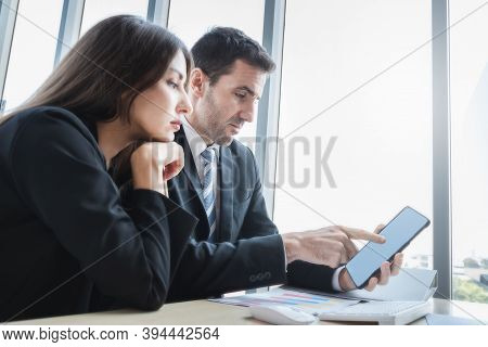 Two Business Colleagues Checking Data About Business With Computer Tablet In The Modern Room Office.