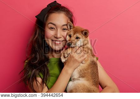 Adorable Cheerful Young Asian Woman Embraces Pet, Feels Happy To Get Popular Japanese Pedigree Dog,