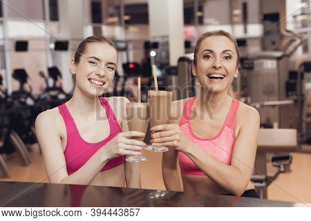 Mother And Daughter Drinking Protein Shakes At Gym. They Look Happy, Fashionable And Fit.