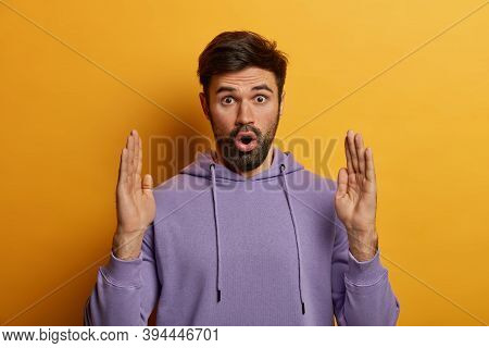 Impressed Bearded Caucasian Man Demonstrates Enormous Huge Object, Raises Hands And Shows Something