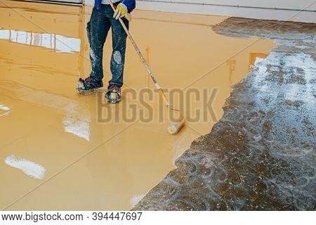 Worker, Coating Floor With Self-leveling Epoxy Resin In Industrial Workshop.