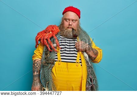 Male Mariner Looks With Scared Expression At Octopus, Afraids Big Sea Creature, Poses With Fishing N