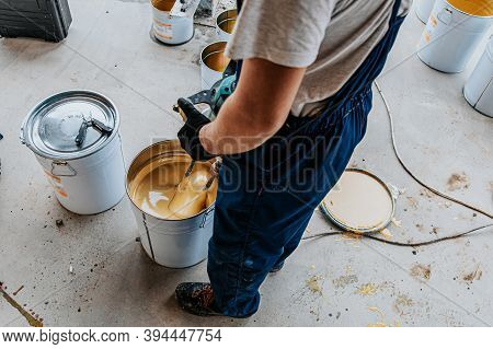 Worker Mixing Yellow Epoxy Resin With The Mixer In A Tin Bucket