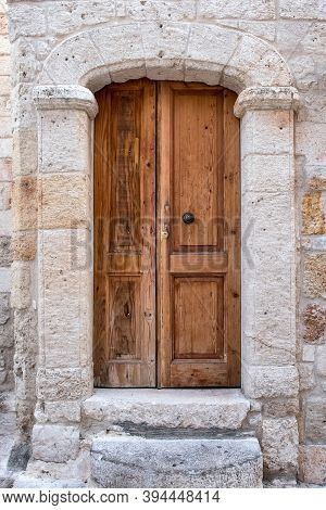 The Stone Portal Of The Building And The Wooden Paneled Door. A Wall Of Rough Stone.
