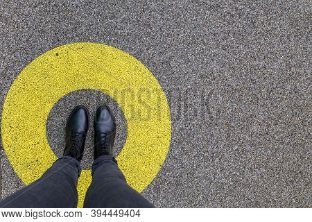 Black Shoes Standing In Yellow Circle On The Asphalt Concrete Floor. Comfort Zone Or Frame Concept.