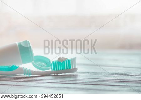Turquoise Toothbrush With White Toothpaste On The Bristles And A Tube Of Toothpaste On A White Woode