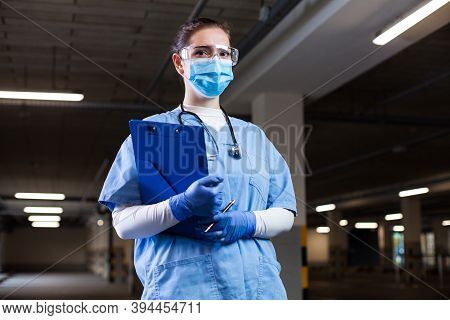 Medical Ems Worker Wearing Ppe Uniform,safety Goggles And Face Mask,holding Clipboard At Mobile Test