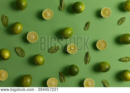 Sour Green Bright Limes Loaded With Nutrients And Fresh Mint On Green Background. Citrus Fruit Can B