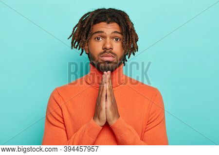 Young Male With Dreadlocks And Hopeful Expression, Beggs And Prays, Keeps Palms Pressed Together, Wo
