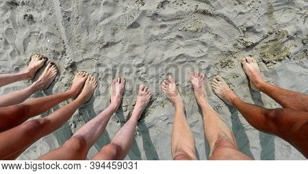 Line Of Ten Feet Of A Family Of Five On The Sand By The Sea In Summer