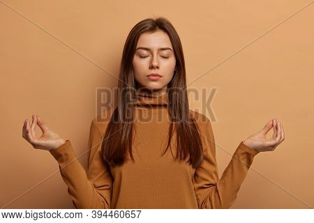 Patient Relieved Woman Makes Mudra Gesture, Meditates Indoor, Tries To Relax, Breathes Deeply And Re