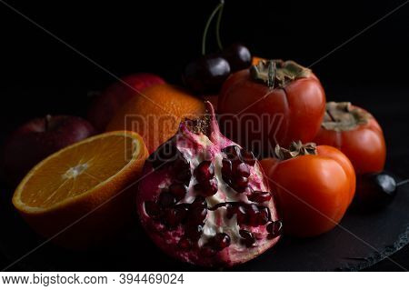 Still Life Of Half A Juicy Pomegranate, Persimmon, Apples, Orange And Sweet Cherry On A Black Backgr