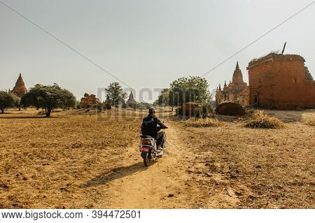 Man Riding An Electric Scooter E-bike Around The Old Temples In Bagan, Myanmar. Pagodas And Spires O
