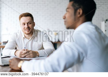 Handsome Happy Young Business Man Explaining To African Partner The Benefits Of New Deal To Colleagu
