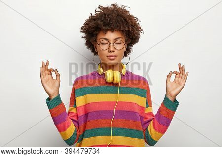 Relaxed Beautiful Lady With Afro Hairstyle Meditates Indoor, Keeps Eyes Closed, Feels Satisfied Lo L