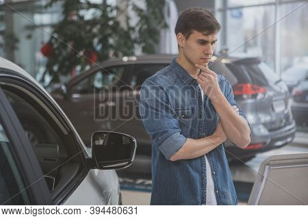 Young Attractive Man Looking At New Car Far Sale Thoughtfully, Rubbing His Chin. Handsome Male Custo
