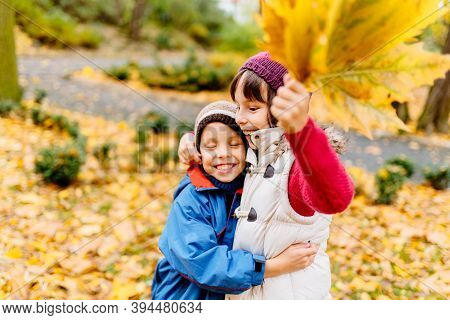 Funny Cute Little Boy And Girl Hugging In Autumn Park, Happy Cheerful Kids Brother With Sister Havin