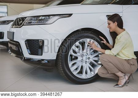 Full Length Shot Of A Beautiful Elegant Woman Examining Wheels And Tires Of A Car She Is Buying, Cop
