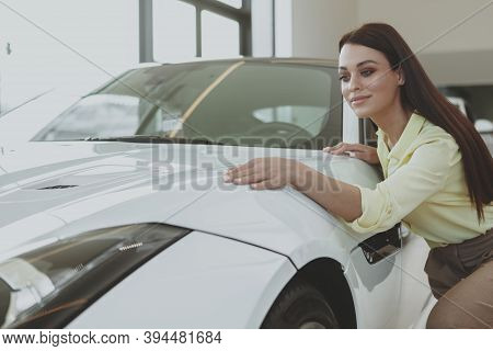 Beautiful Cheerful Dark Haired Elegant Woman Checking Out Stunning White Sportscar At The Dealership