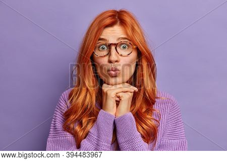Close Up Shot Of Good Looking Romantic Young Woman With Natural Ginger Hair Keeps Lips Folded In Kis