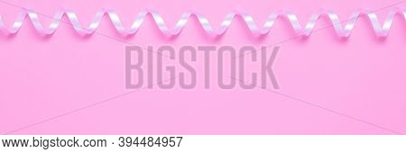 Pink Festive Background With Shiny Winding Serpentine And Copyspace For Text. A Serpentine Streamer