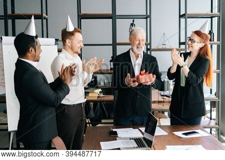 Successful Business Team Of Multi-ethnic People Giving Present To Happy Mature Adult Male Boss. Mult
